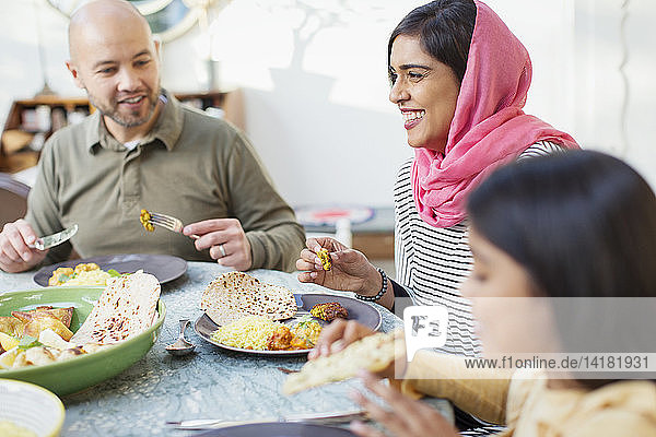 Happy woman in hijab eating dinner with family at table