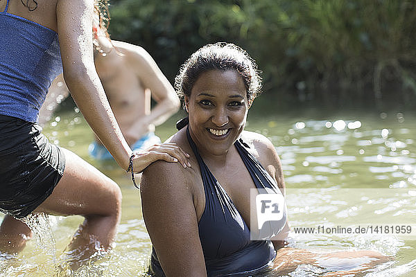 Portrait smiling woman relaxing in sunny river