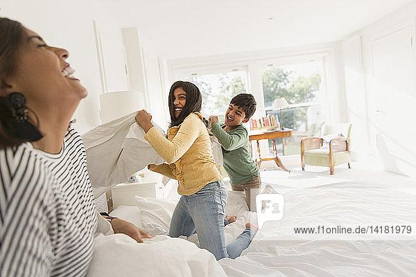 Verspielte Mutter und Kinder genießen die Kissenschlacht auf dem Bett
