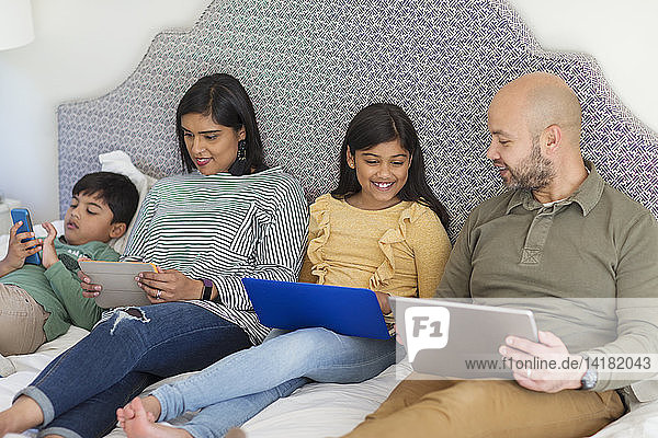 Family using technology on bed