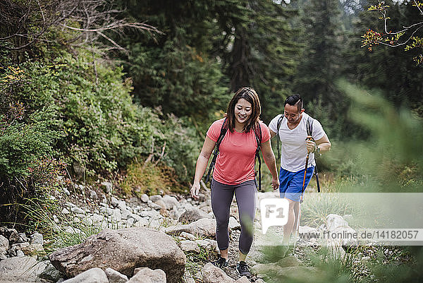 Couple hiking over rocks in woods