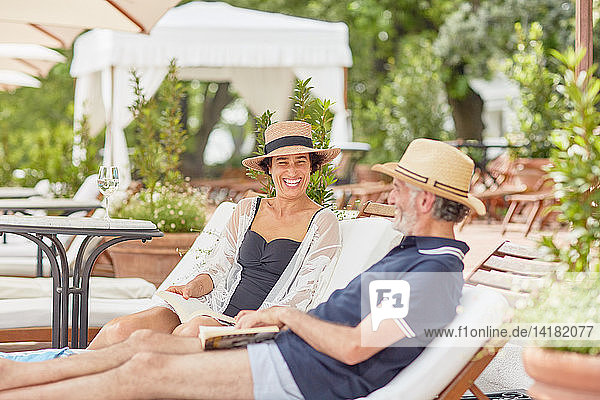 Mature couple reading books  relaxing on lounge chairs at resort poolside