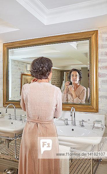Woman getting ready at hotel bathroom mirror