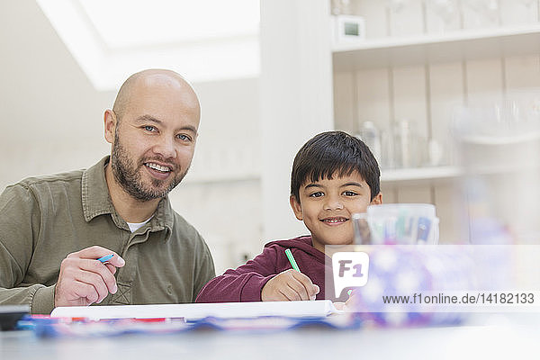 Portrait happy father and son coloring at table