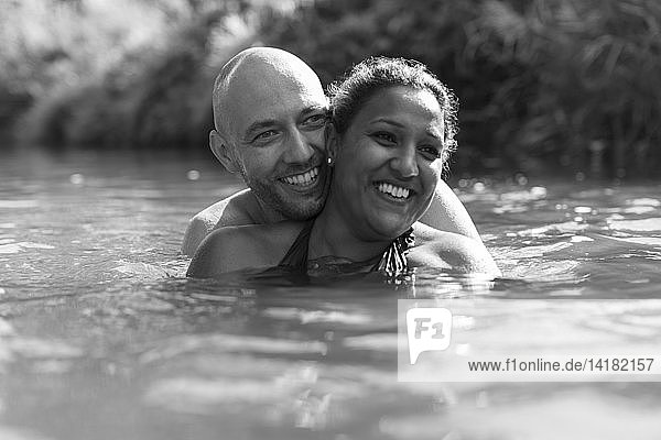 Happy couple swimming in river