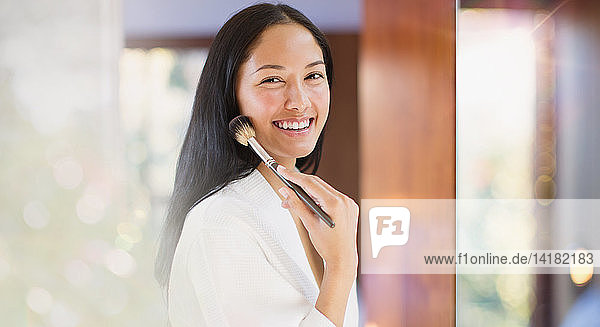 Portrait confident young woman applying makeup