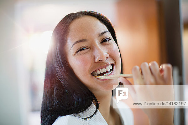 Portrait happy young woman brushing teeth