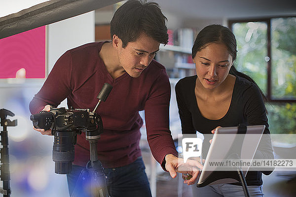 Photographers using digital tablet and camera in studio