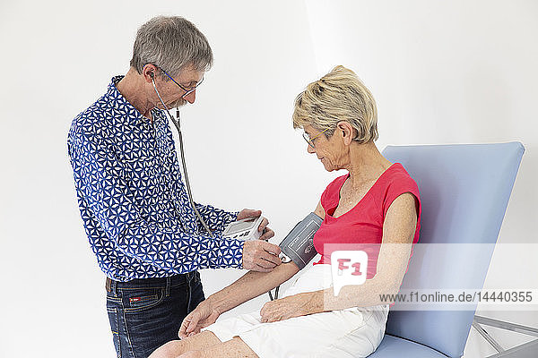Woman consulting a doctor who is taking her blood pressure.