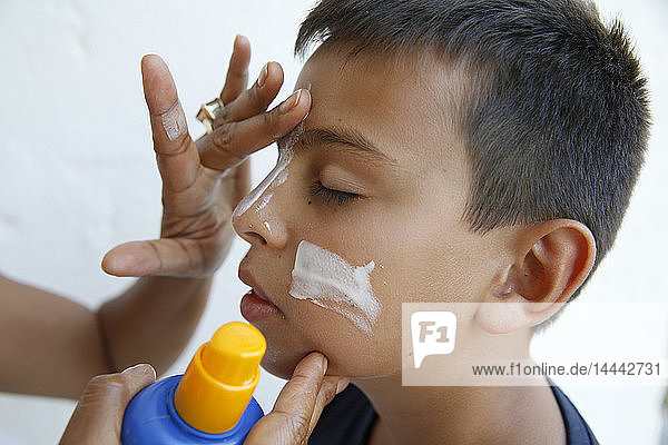Mother putting sun protection cream on her son's face in Salento,  Italy.