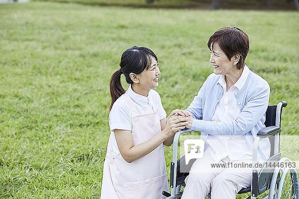 Japanese caretaker helping senior patient