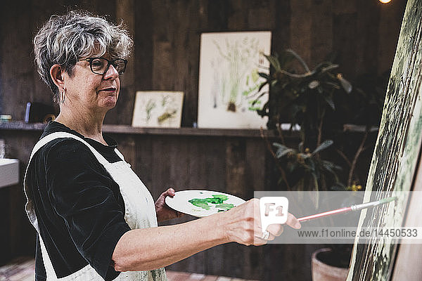 Senior woman wearing glasses  black top and white apron standing in studio  working on painting of trees in forest.