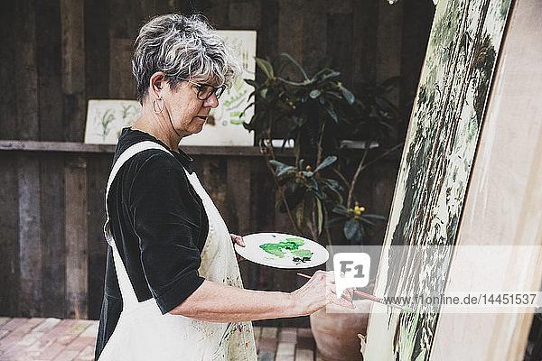 Ältere Frau mit Brille  schwarzem Oberteil und weißer Schürze steht im Atelier und arbeitet an der Bemalung von Bäumen im Wald.