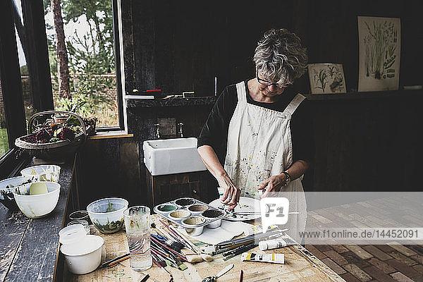 Ältere Frau mit Brille  schwarzem Oberteil und weißer Schürze steht im Atelier und mischt Farben.