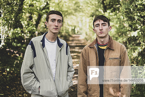 Young man and teenage boy with short brown hair wearing casual jackets standing side by side on a forest path  looking at camera.