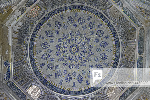 Das Innere  die blau-weiß gemusterten Wände und die Kuppel eines Madrasa-Gebäudes in Samarkand.