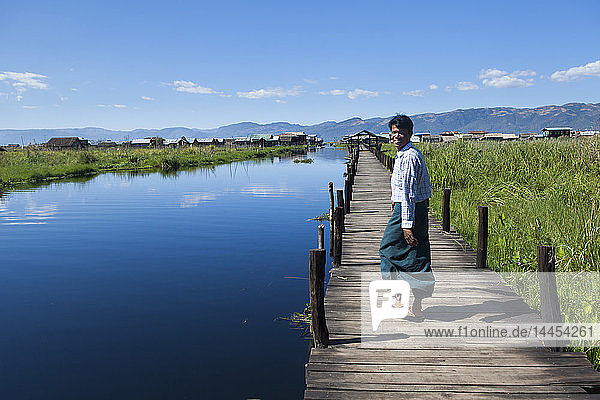 Man wearing a longyi walking on a footbridge above the Inle lake  Nyaungshwe  Burma