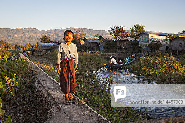 Child wearing a longyi walking on a footbridge built above the Inle Lake  Nyaungshwe  Burma