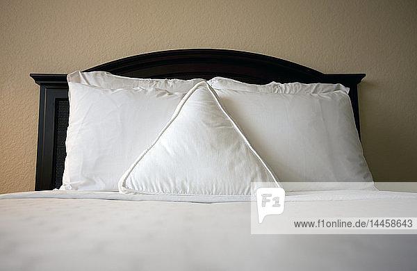 Dreieckiges Kissen auf dem Bett