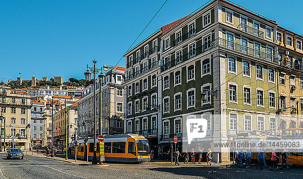 Traditional trams at Praca da Figueira with Castelo Sao Jorge on the far left  Lisbon  Portugal