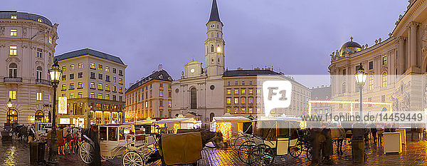 Christmas Market stalls and St. Michael Catholic Church in Michaelerplatz  Vienna  Austria
