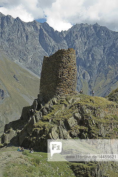 Tourists trekking by a tower near the Gergeti Holy Trinity Church by the river Chkheri  under Mount Kazbegi at an elevation of 2170 meters in the Caucasus  Georgia  Central Asia