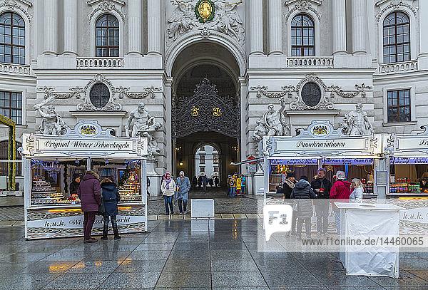 Shoppers at Christmas market stalls in Michaelerplatz  Vienna  Austria