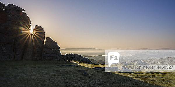 Sun breaks through a gap in granite rocks at Haytor in Dartmoor National Park  Bovey Tracey  Devon  England  United Kingdom