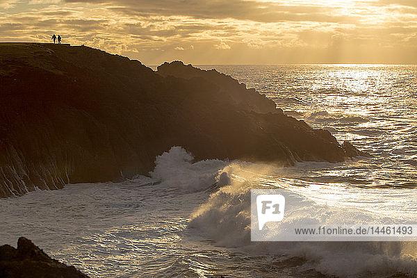 A couple enjoy the view of sunset and crashing waves  Newport  Oregon  USA