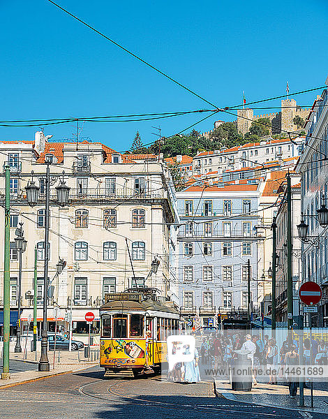 Traditional yellow tram at Praca da Figueira with Castelo Sao Jorge at background  Lisbon  Portugal