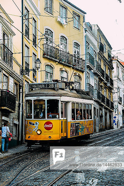 Traditional yellow electric tram in a narrow street in Alfama  Lisbon  Portugal
