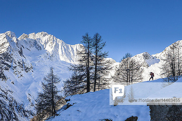 Photographer at the foot of snowy Monte Vazzeda  Alpe dell'Oro  Valmalenco  Valtellina  Sondrio province  Lombardy  Italy