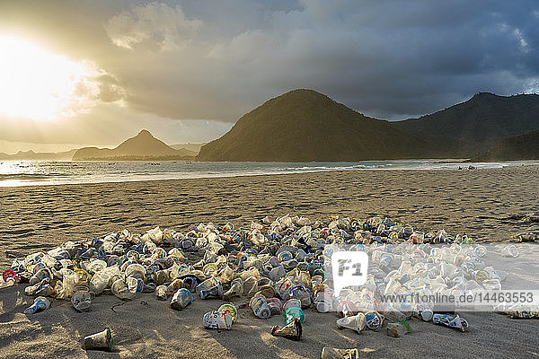 Pile of plastic rubbish dumped on the sand at sunset on Selong Belanak Beach on Lombok  Indonesia  Southeast Asia