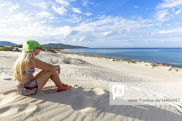 Young girl looks at the sea from a sand dune  Is Arenas Biancas  Teulada  Cagliari province  Sardinia  Italy  Mediterranean  Europe