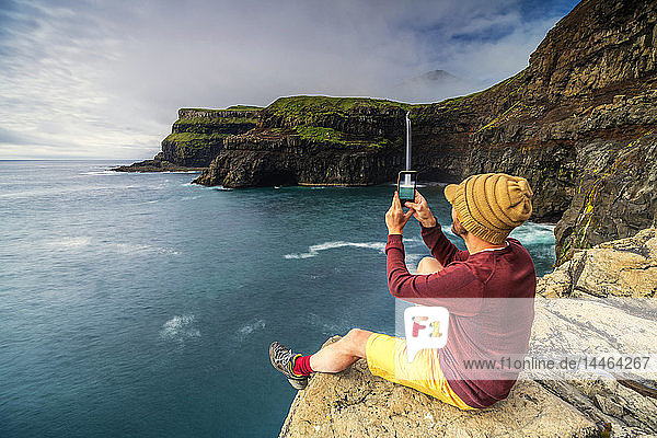 Man with smartphone snaps photos at Gasadalur waterfall  Vagar island  Faroe Islands  Denmark