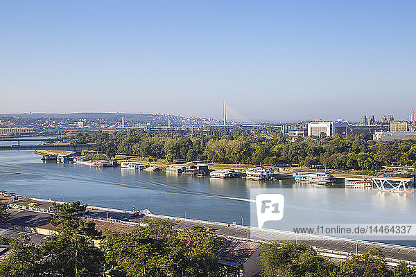 View of floating bars and nightclubs on Sava River  New Belgrade with Ada bridge in the distance  Belgrade  Serbia