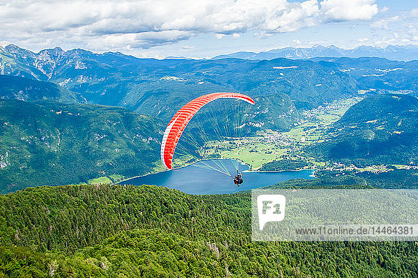 Paraglider sails over Lake Bohinj and its mountains  Slovenia
