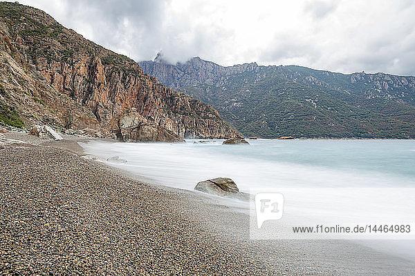 A slow exposure of waves breaking on a pebble beach in Calvi  Corsica  France  Mediterranean