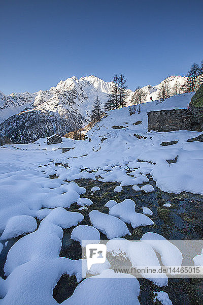 Snow on rocks along the creek with Monte Vazzeda on background  Alpe dell'Oro  Valmalenco  Valtellina  Lombardy  Italy