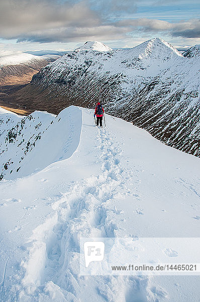 A female walker descending from the summit of Stob Dubh on Buchaille Etive Beag on a crisp winter day  Highlands  Scotland  United Kingdom