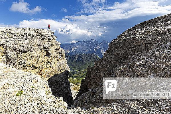 Hiker looks towards Marmolad  Piz Pordoi  Pass Pordoi  Fassa Valley  Trentino  Dolomites  Italy