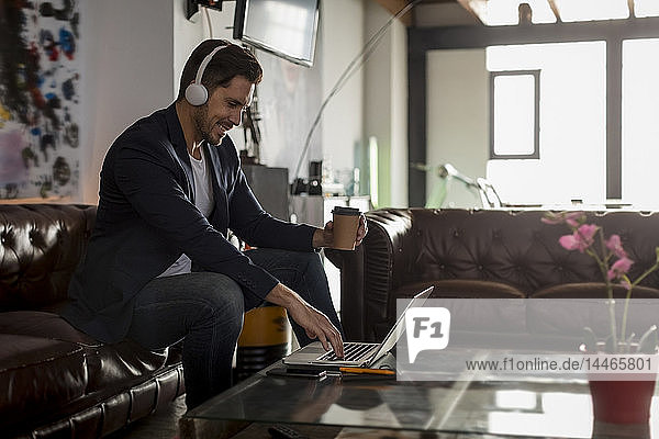 Smiling man with headphones and takeaway coffee sitting on couch using laptop