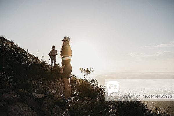 Südafrika  Kapstadt  Kloof Nek  zwei Frauen auf einem Wanderweg bei Sonnenuntergang