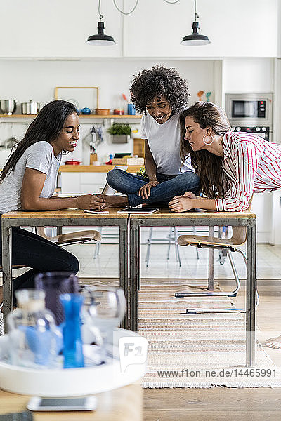 Drei lächelnde Frauen schauen zu Hause auf die Tablette auf dem Tisch