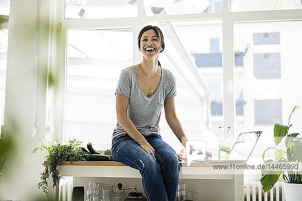 Frau sitzt am Küchentisch  sucht nach gesunden Rezepten  benutzt Laptop