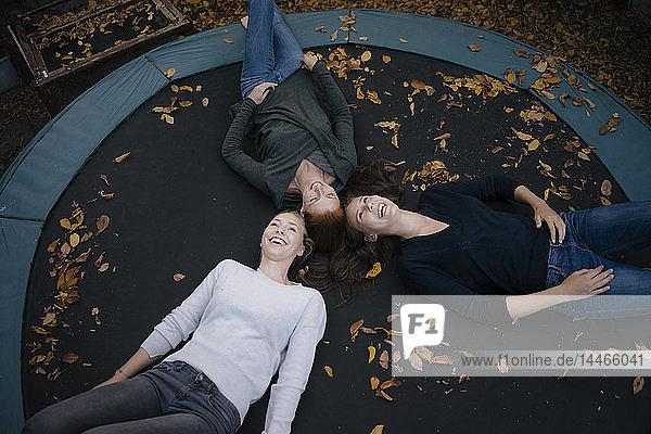 Glückliche Mutter mit zwei Mädchen im Teenageralter,  die im Herbst auf dem Trampolin liegen