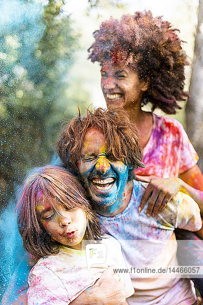 Family full of colorful powder paint  celebrating Holi  Festival of Colors