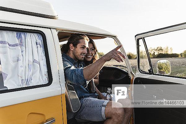 Glückliches Paar sitzt in seinem Wohnwagen  Mann zeigt auf Distanz