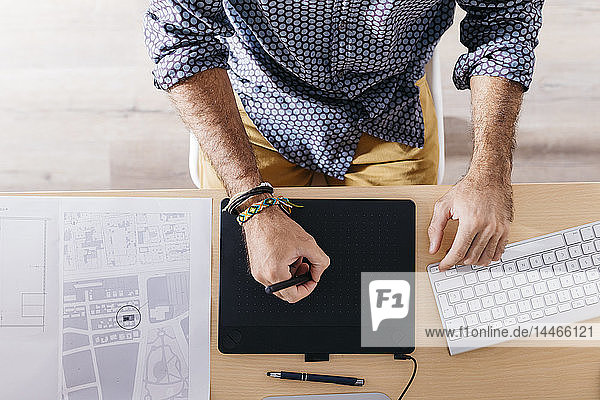 Close-up of man working at home using graphics tablet