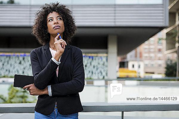 Porträt einer denkenden Geschäftsfrau mit Notizbuch und Stift im Freien